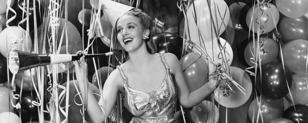 Retro image of girl having a party, with balloons in the background
